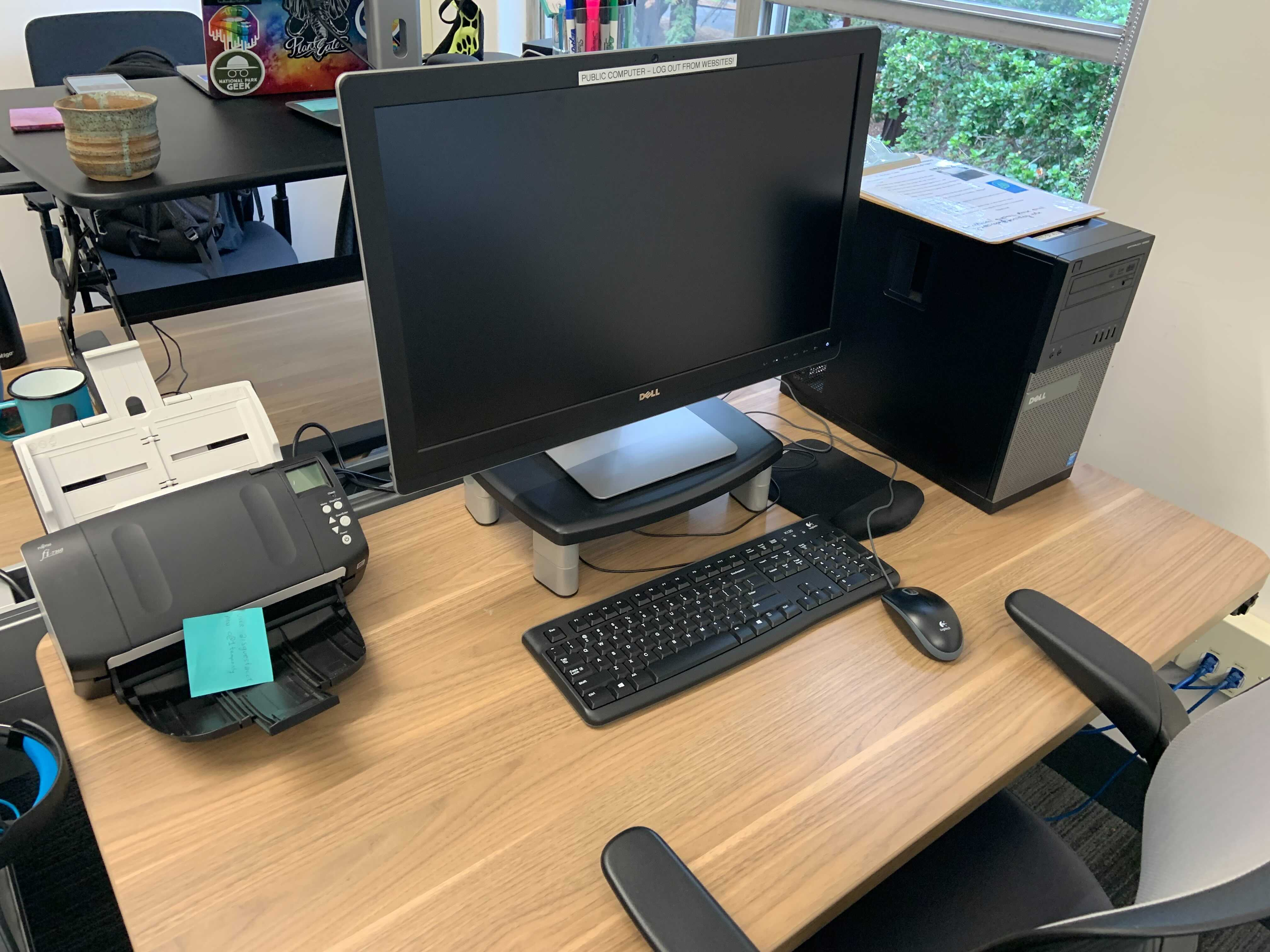 A desktop computer, keyboard, mouse, and scanning device on a desk in the Academic Innovation Studio.